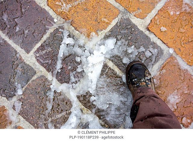 Shoe on wet snow / sleet on slippery pavement / sidewalk in winter