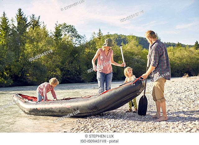 Family pulling dinghy onto riverbank, holding paddle boards