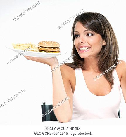 Woman holding a hamburger plate and smiling
