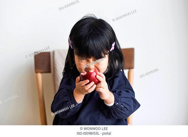 Little girl biting into apple