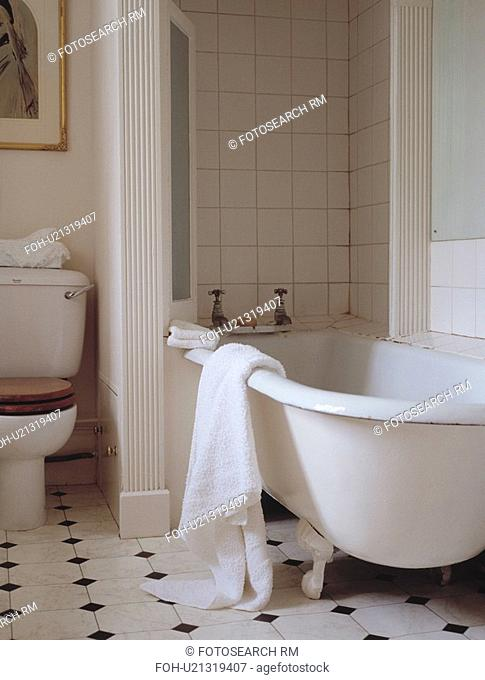 White towel on the side of clawfoot bath in traditional bathroom with ceramic tiled floor