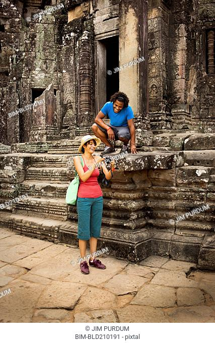 Couple visiting ancient temple, Angkor, Siem Reap, Cambodia