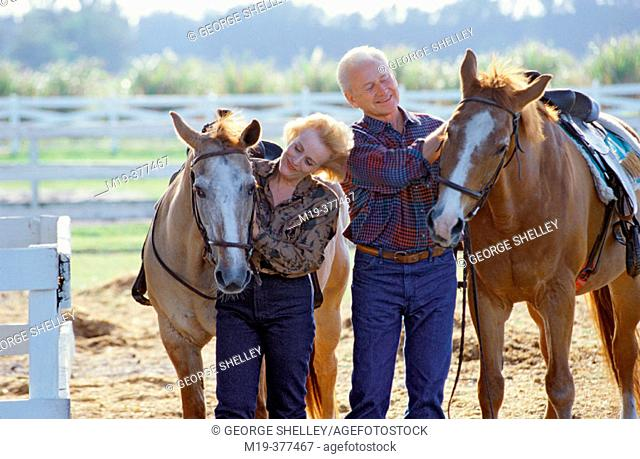 mature couple with horses