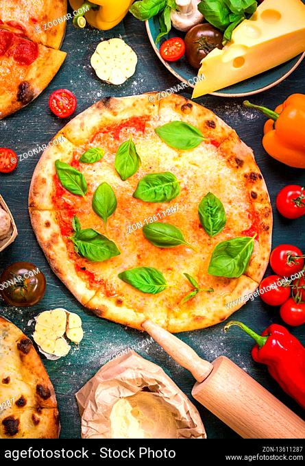 Delicious baked pizza and ingredients for making pizza. Flour, cheese, tomatoes, basil, pepperoni, mushrooms and rolling pin over wooden background