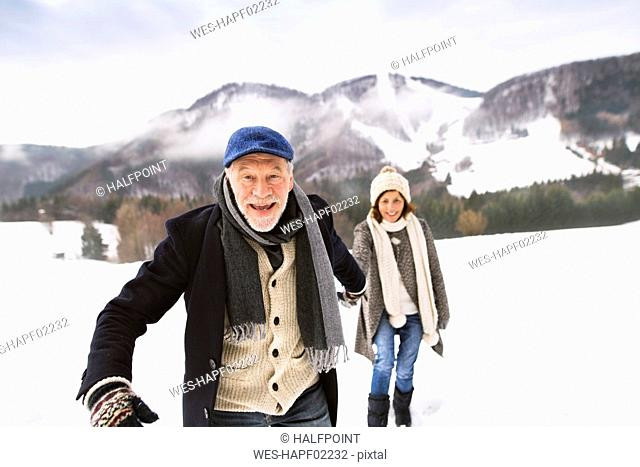 Portrait of senior man walking hand in hand with his wife in snow-covered landscape