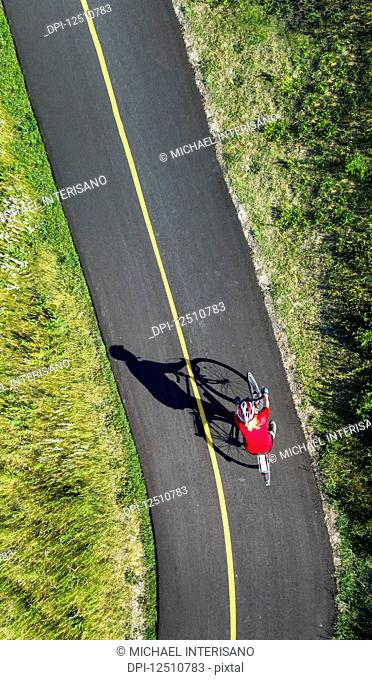 View from directly above a cyclist in a red shirt on a paved cycling trail; Calgary, Alberta, Canada