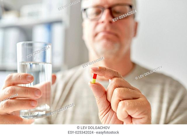 age, medicine, healthcare and people concept - close up of senior man hands with pill and water glass at home