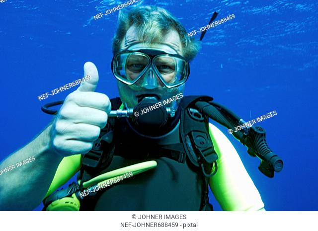 A diver in blue water doing thumbs up, Egypt