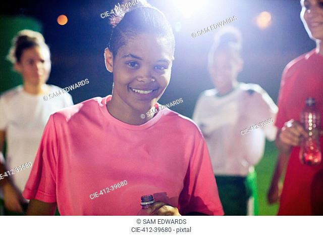 Portrait confident young female soccer player on field with teammates at night