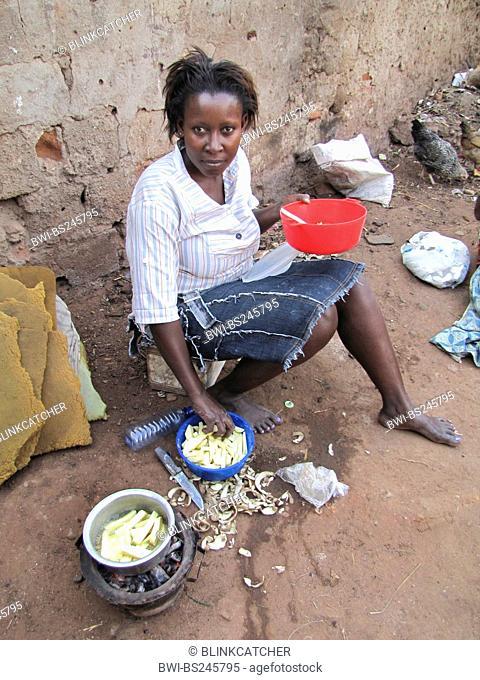 woman is frying potato chips on the soil ground of a backyard, Burundi, Bujumbura mairie, Bwiza, Bujumbura
