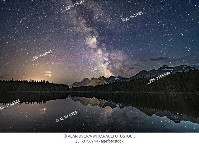 Mars (at left in clouds) and the summer Milky Way over Lake Herbert and reflected in the still waters this night. This is in Banff National Park, Alberta
