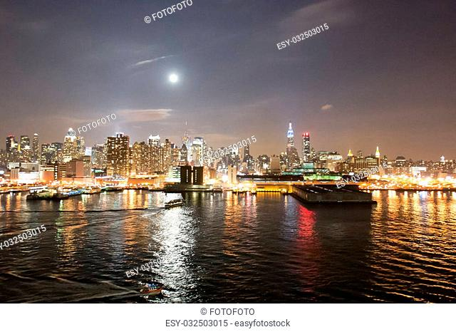 The panorama of Midtown Manhattan coast viewed from the Hudson River at night in New York City, USA