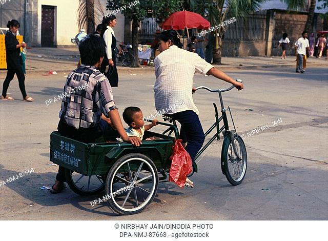Man riding cycle rickshaw , Xishuangbanna , Kunming , Yunnan , China