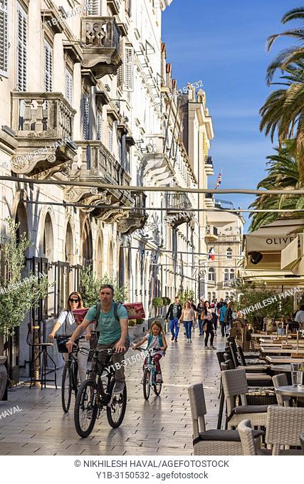 Family bicycling on Riva, Split, Croatia