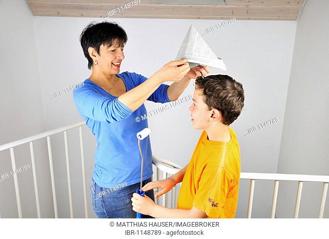 Paintwork, woman putting a paper hat on her son's head