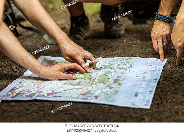 A group of hikers uses map and compass to navigate through the forest
