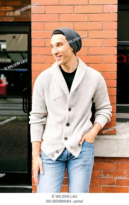 Young man leaning against brick wall, Vancouver, Canada