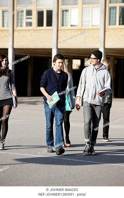 Teenagers walking on schoolyard