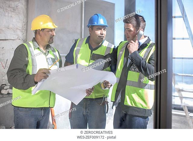 Architect and construction workers discussing construction plan