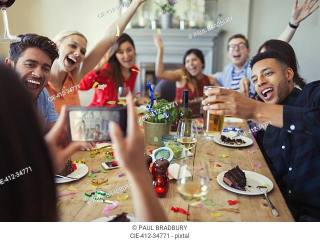 Woman with camera phone photographing playful friends throwing confetti at restaurant table
