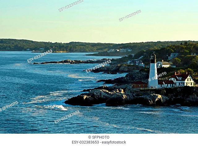 historic Portland Head lighthouse in Cape Elizabeth, Maine, overlooking the Casco Bay in the Gulf of Maine; seen from the ocean in evening light