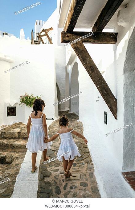 Spain, Balearic Islands, Menorca, Binibeca, back view of two little sisters walking hand in hand