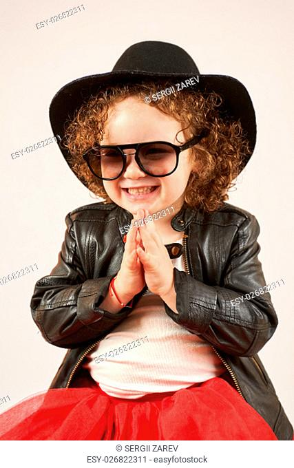 Little girl with black hat and Sunglasses sitting and smiling
