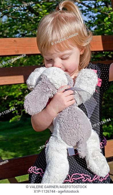 This precious shot image shows a Caucasian 2 year old girl kissing her favorite stuffed animal, a white and gray plush dog You can tell by her facial expression...