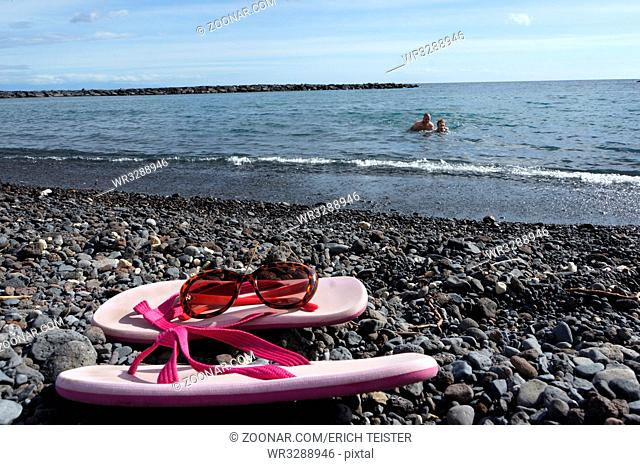 Flip-Flops und Sonnenbrille am Kiesstrand, Güimar, Teneriffa, Kanaren, Spanien, Puertito de Güimar