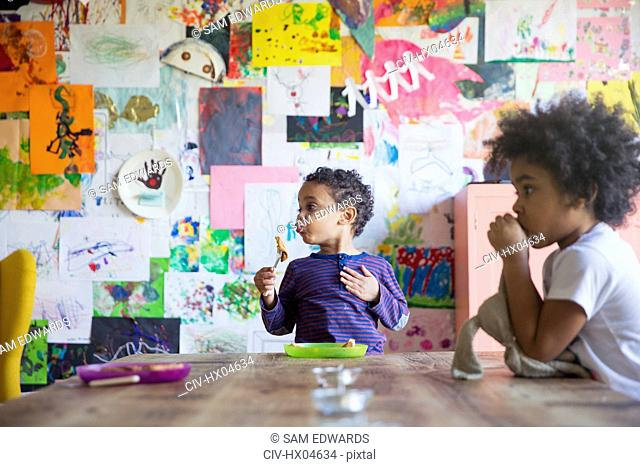 Toddler brother and sister eating at dining table