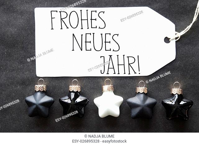 Label With German Text Frohes Neues Means Happy New Year. Black And White Christmas Tree Balls On Black Paper Background