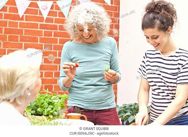 Three women preparing fresh food at garden table