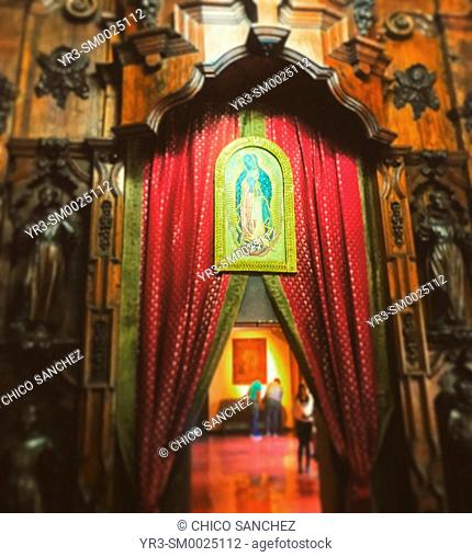A door decorated with a red curtain and an image of Our Lady of Guadalupe decorates the Museum of the Our Lady of Guadalupe Basilica in Mexico City, Mexico