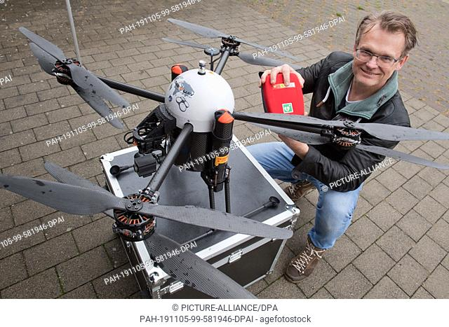 04 November 2019, Mecklenburg-Western Pomerania, Penkun: Jörg Brinkmeyer, drone pilot of GLOBE UAV GmbH, attaches a defibrillator to a hexakopter (drone)