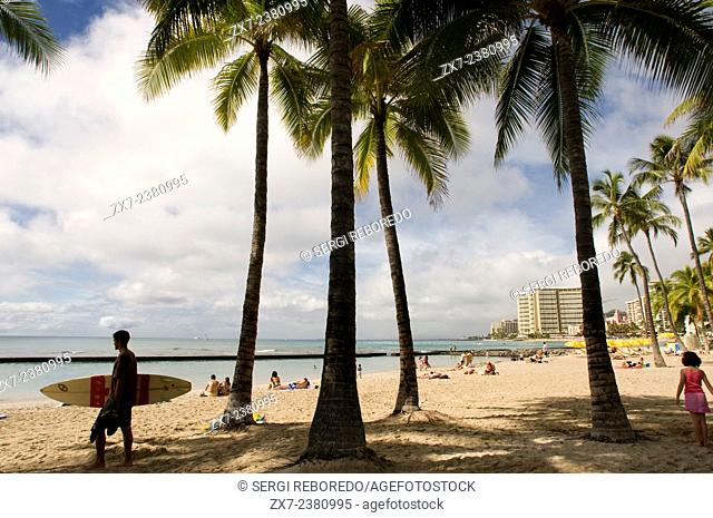 Surfer on the famous Waikiki Beach. Kalakaua Avenue. O'ahu. Hawaii. Located on the south shore of Honolulu, the world-famous neighborhood of Waikiki was once a...