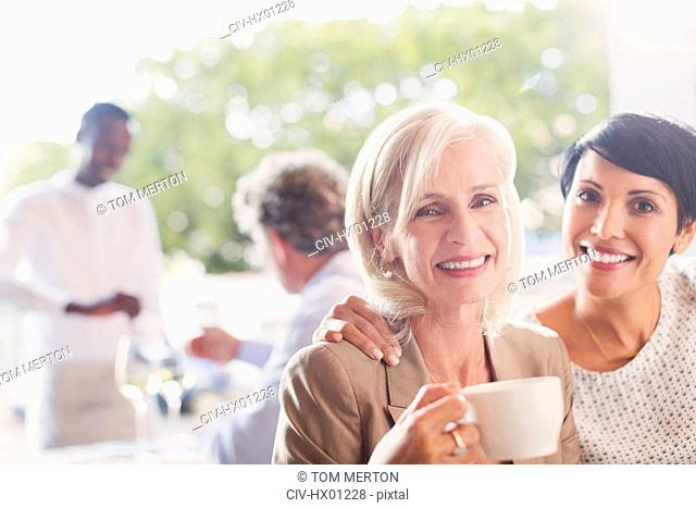 Portrait smiling mother and daughter drinking coffee in restaurant