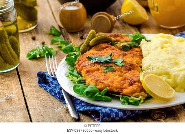 Wiener Schnitzel, served with baked potatoes, pickled cucumbers and freshly squeezed orange juice