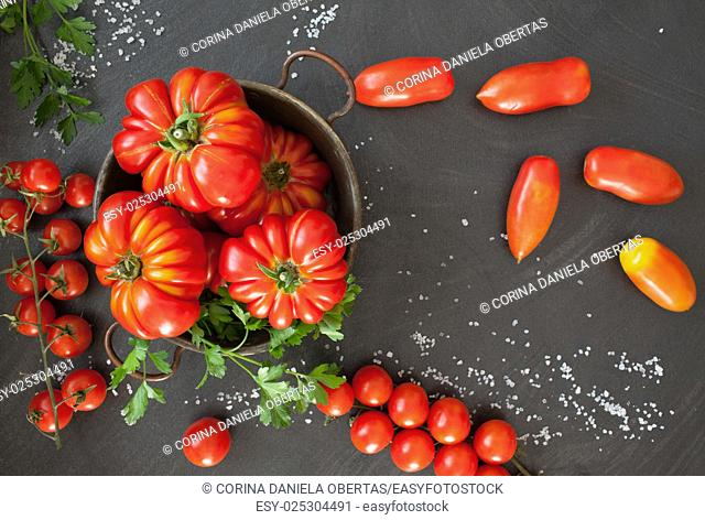 Three different types of tomatoes on black background