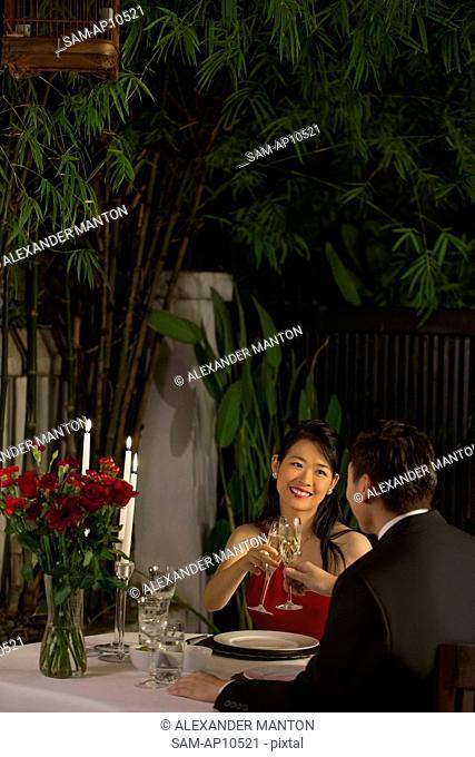 Singapore, Couple making toast in restaurant