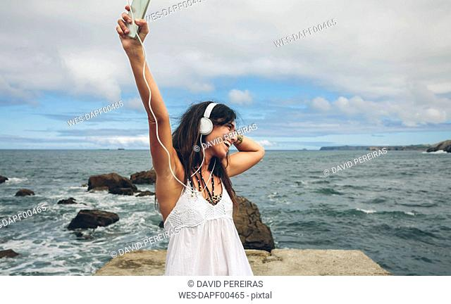 Happy woman on a pier listening music with headphones