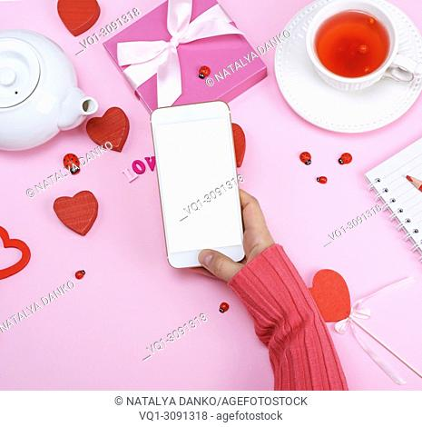 right female hand in a pink sweater is holding a white smartphone with an empty white screen over a pink table with a cup of tea and a kettle, top view