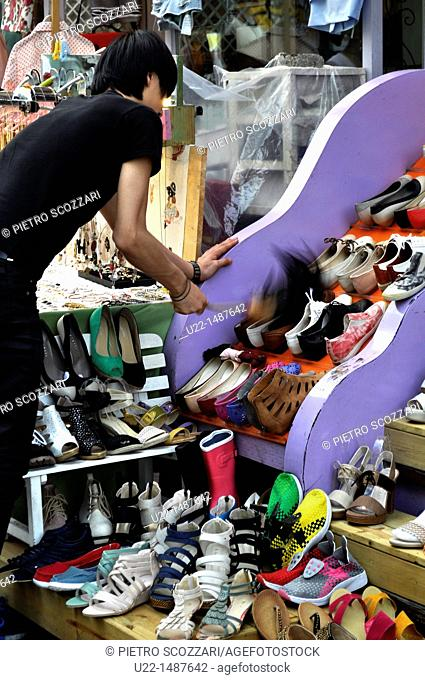 Seoul (South Korea): a seller dusting his shop shoes in Mapo-gu