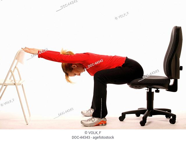 fit in the ofice - young woman sitting on an ofice chair doing gymnastics - upper body to the upper legs and stretching the arms to the front on an other chair...