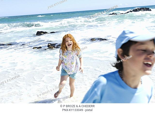 Boy and little girl walking on the beach, outdoors