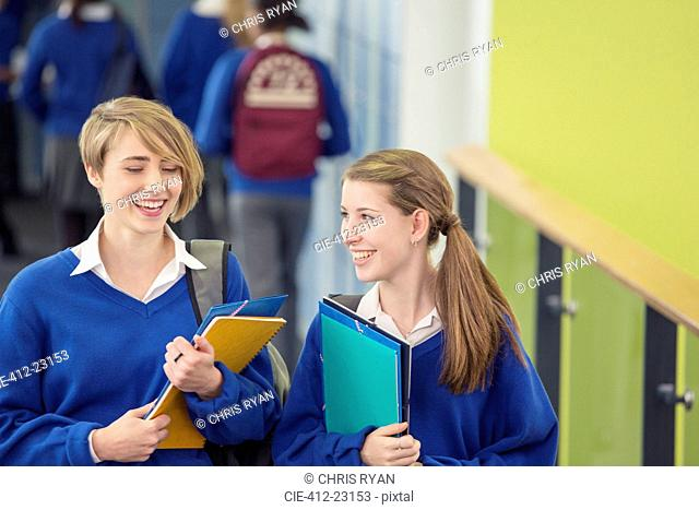 Two smiling female students wearing school uniforms walking through school corridor