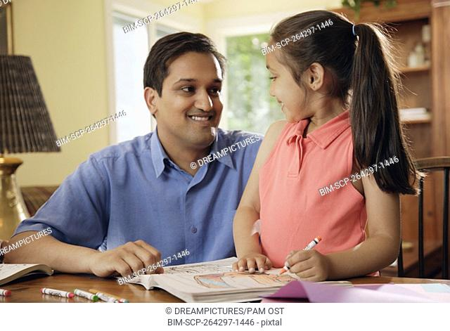 Indian father helping daughter with homework