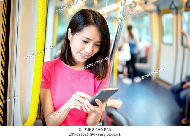 Woman using mobile phone inside train