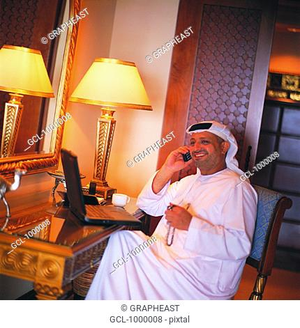 Arab businessman using mobile phone and laptop