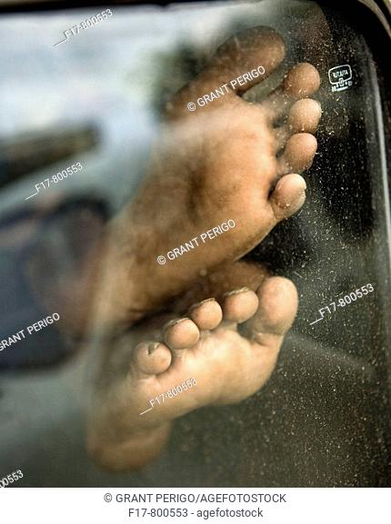 close up colorful shot of a cab drivers feet in car window taking a nap.