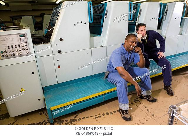 Portrait of two men in coveralls sitting in front of a printing machine